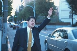 タクシーを止めようとしているビジネスマンの写真素材 [FYI03863362]