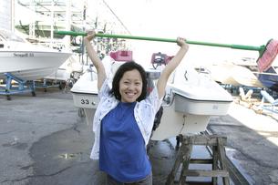 掃除用ブラシを頭上に持ち上げる日本人の女の子の写真素材 [FYI03863667]