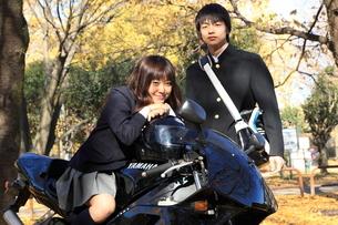 男子高生とバイクに跨る女子高生の写真素材 [FYI03863924]