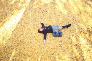 イチョウの絨毯に寝そべる女子高生の写真素材 [FYI03863926]
