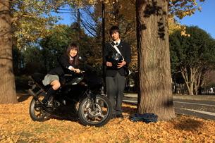 イチョウの木の下でバイクに跨る女子高生と男子高生の写真素材 [FYI03863933]