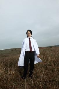 草むらに立つ日本人青年医師の写真素材 [FYI03863950]