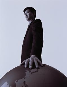 地球儀に手を置く日本人ビジネスマン B/Wの写真素材 [FYI03864135]