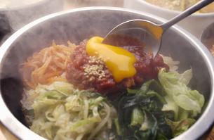 韓国料理のユッケビビンバを混ぜるの写真素材 [FYI03864255]