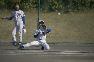 膝をついてボールをキャッチする少年の写真素材 [FYI03865976]