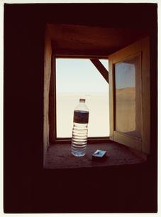 窓辺に置かれたペットボトルとタバコの写真素材 [FYI03867715]
