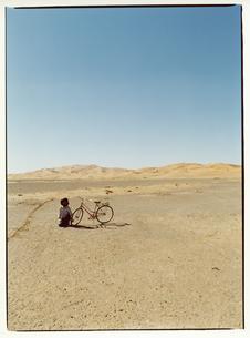 自転車のそばに座る外国人の男性 サハラ砂漠 モロッコの写真素材 [FYI03867723]