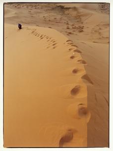 サハラ砂漠を歩く人物と足跡 モロッコの写真素材 [FYI03867747]