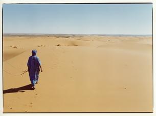 サハラ砂漠を歩く外国人男性 モロッコの写真素材 [FYI03867756]