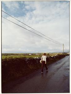 田舎道を歩く外国人女性の後姿 ゴールウェイ アイルランドの写真素材 [FYI03867766]