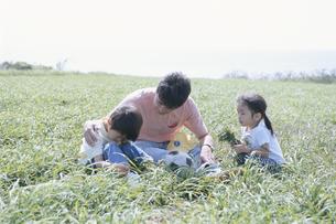 野原に座る日本人の父と息子と娘の写真素材 [FYI03867967]