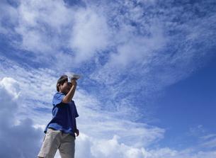 紙飛行機で遊ぶ日本人の男の子と空の写真素材 [FYI03867999]