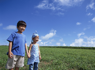 野原で笑う日本人の男の子と女の子と青空の写真素材 [FYI03868000]