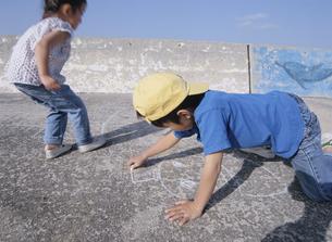 道にラクガキする日本人の男の子と女の子の写真素材 [FYI03868015]