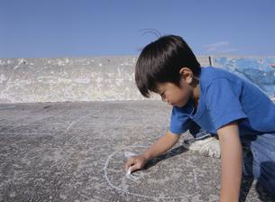 道にラクガキする日本人の男の子の写真素材 [FYI03868016]