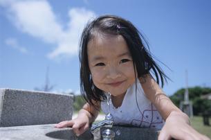 公園の水飲み場で微笑む日本人の女の子の写真素材 [FYI03868032]