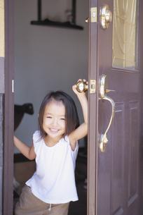 玄関のドアを開ける日本人の女の子の写真素材 [FYI03868062]