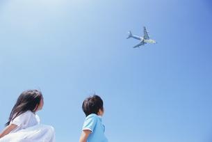 飛行機を見つめる女の子と男の子の写真素材 [FYI03868195]