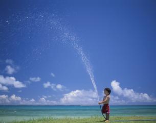 ホースで水をまく男の子の写真素材 [FYI03868283]