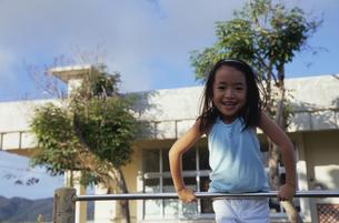 鉄棒で遊ぶ笑顔の女の子の写真素材 [FYI03868336]