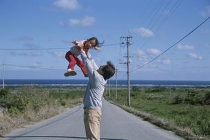 道路で女の子を持ち上げる父親の写真素材 [FYI03868412]