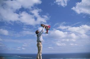 丘の上で女の子を抱き上げる父親の写真素材 [FYI03868430]
