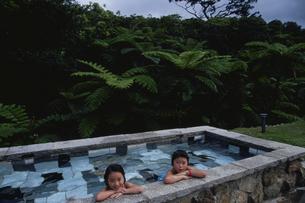 ジャングルの露天風呂に入る子供の写真素材 [FYI03868469]