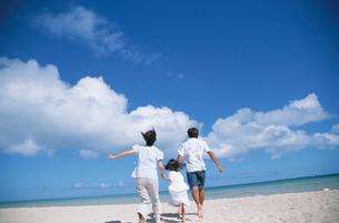ビーチを走る家族の後ろ姿と入道雲の写真素材 [FYI03868491]
