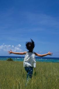 草むらを走る女の子の後ろ姿の写真素材 [FYI03868494]