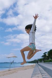 ビーチでジャンプする女の子の写真素材 [FYI03868523]