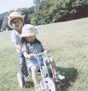 女の子の乗る三輪車を押す男の子 日本人の写真素材 [FYI03868557]