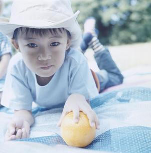 敷物に寝そべりオレンジを掴む帽子を被った日本人の男の子の写真素材 [FYI03868560]