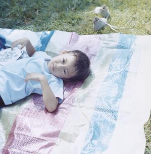 芝生の上の敷物に寝転がる日本人の男の子の写真素材 [FYI03868563]