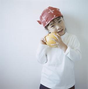 グレープフルーツを持つバンダナを巻いた日本人の女の子の写真素材 [FYI03868568]