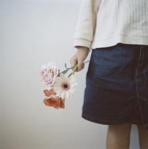 3輪の花を握る女の子の手の写真素材 [FYI03868573]