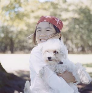 公園で犬を抱えた日本人の女の子の写真素材 [FYI03868576]