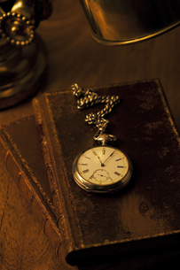 書斎のデスクの本と懐中時計の写真素材 [FYI03868794]