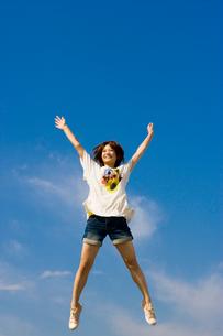 青空と元気にジャンプする女子大学生の写真素材 [FYI03868811]