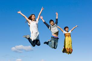 青空とジャンプする3人の大学生の写真素材 [FYI03868822]