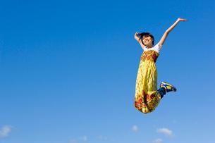 青空とジャンプする若い女子大学生の写真素材 [FYI03868824]