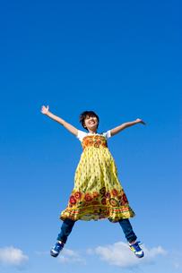 青空とジャンプする若い女子大学生の写真素材 [FYI03868826]