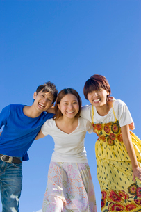 肩を組んで笑う若い男女3人の大学生と青空の写真素材 [FYI03868839]