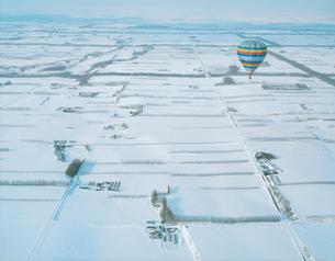 雪原の中を飛ぶ熱気球の写真素材 [FYI03869086]