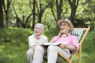 庭で新聞を読む日本人シニア夫婦の写真素材 [FYI03869113]