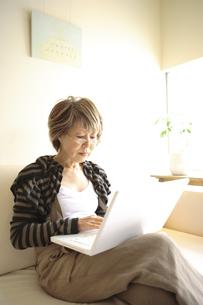 ソファに座ってパソコンを見るシニア女性の写真素材 [FYI03869133]