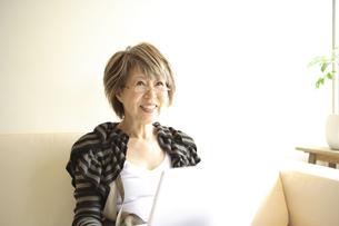 ソファに座ってパソコンを見るシニア女性の写真素材 [FYI03869134]