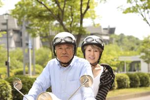 スクーターに乗るシニア夫婦の写真素材 [FYI03869140]