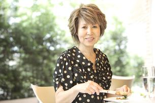 オープンレストランで食事しているシニア女性の写真素材 [FYI03869155]