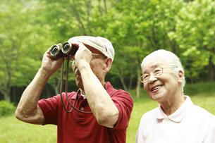 双眼鏡を覗くシニア夫婦の写真素材 [FYI03869169]