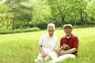 芝生に座り犬を抱くシニア夫婦の写真素材 [FYI03869171]